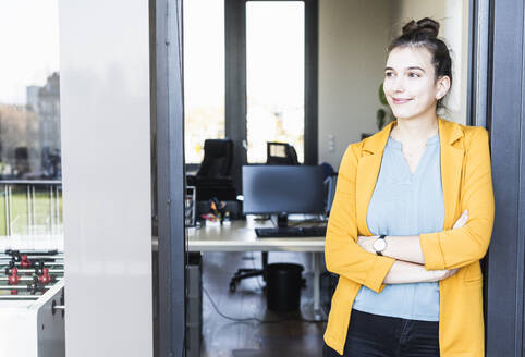 Smiling businesswoman standing with arms crossed at office entrance - UUF22105