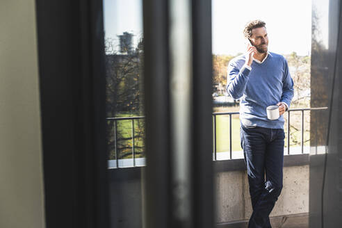 Businessman with coffee cup talking on mobile phone while standing at office balcony - UUF22114