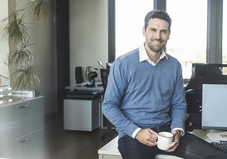 Smiling businessman drinking coffee while sitting on table at office - UUF22120