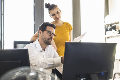 Businessman and woman using computer while working in office - UUF22129