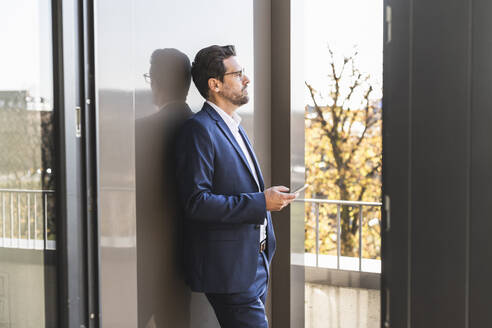 Businessman using mobile phone while standing by balcony at office - UUF22141