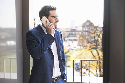Mature businessman talking on mobile phone while standing by balcony at office - UUF22144
