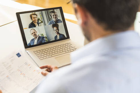 Businessman holding paper while attending video conference with team on laptop at office - UUF22162