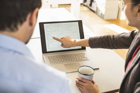Businesswoman with coffee cup explaining diagram on laptop to businessman while sitting at office - UUF22165