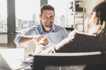 Smiling businessman giving fist bump to colleague while sitting at office - UUF22171