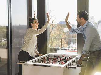 Businessman and woman giving high-five while playing Foosball at office - UUF22183