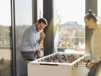 Smiling man showing winning gesture while playing Foosball with colleague at office - UUF22186