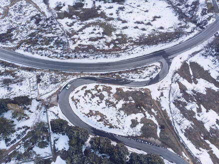 Aerial view of lone car driving along empty highway in Sierra de Guadarrama range - RSGF00445