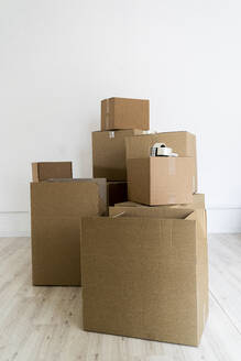 Stack of cardboard boxes against wall in empty room - GIOF09681