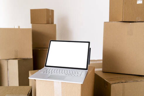 Laptop on cardboard box in living room of new house - GIOF09687