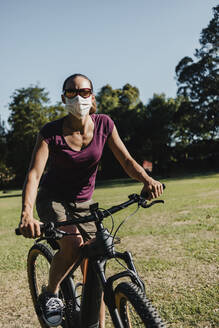 Woman in face mask riding electric mountain bike at park - DMGF00308