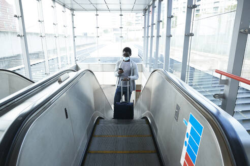 Businessman with luggage using smart phone while standing on escalator at railroad station during COVID-19 - PMF01567