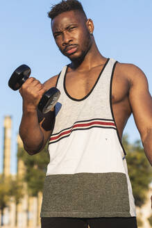 Confident man looking away while exercising with dumbbell at park - PNAF00214