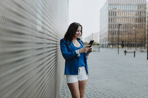 Smiling businesswoman using smart phone while standing on footpath in city - GMLF00820