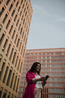 Female entrepreneur text messaging on smart phone while standing against buildings - GMLF00841