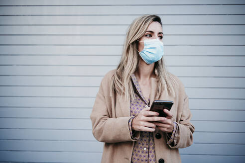 Beautiful blond woman wearing protective face mask while holding mobile phone against wall - EBBF01582