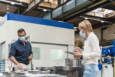 Male entrepreneur examining machinery while female holding digital tablet standing in factory during pandemic - DIGF13321