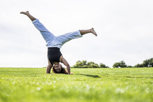 Sportswoman doing handstand on grass in park against clear sky - ABAYF00025