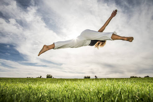 Sportswoman doing acrobatic activity in park against cloudy sky - ABAYF00028