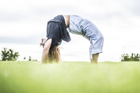 Female acrobat bending over backwards in park - ABAYF00031