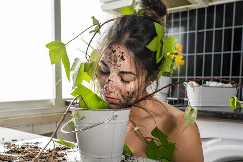 Woman covered with plant leaf smelling potted plant mud at home - GGGF00215