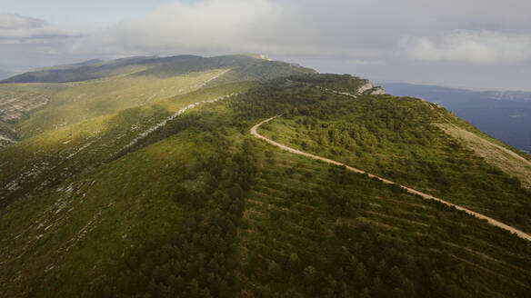 Aerial view of winding road stretching along edge of mountain - OCAF00551