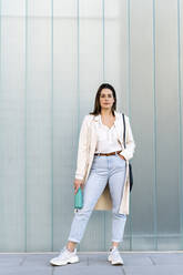 Stylish female entrepreneur with hand in pocket standing against glass wall - AFVF07638