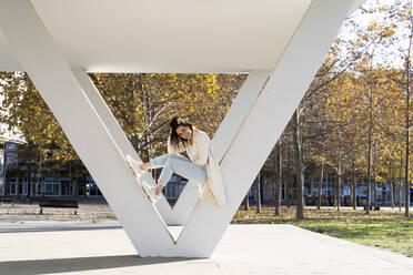 Female entrepreneur with hand in hair leaning on column in park  - AFVF07653