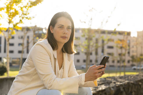 Businesswoman holding smart phone looking away while sitting in city - AFVF07671