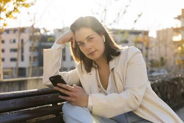 Thoughtful female entrepreneur holding smart phone while sitting on bench - AFVF07677
