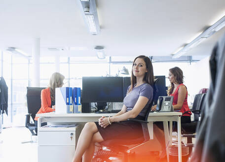 Smiling businesswoman sitting with female colleagues in office - AJOF00655