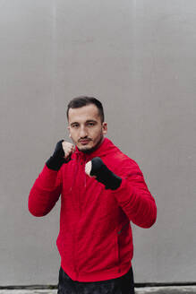 Confident sportsman with bandaged hand boxing while standing against wall - FMOF01235