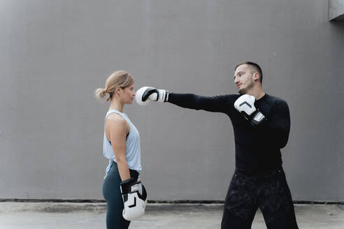 Sportsman teaching boxing to woman while standing against wall - FMOF01241