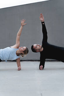 Couple stretching arms while doing side plank pose against wall - FMOF01265