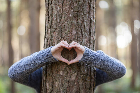 Woman embracing tree and making heart shape in Cannock Chase forest - WPEF03669