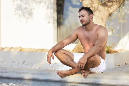 Shirtless young man in shorts meditating at poolside - UKOF00073