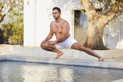 Shirtless handsome young man stretching at poolside - UKOF00076