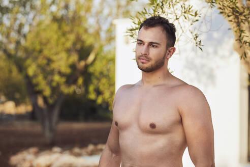 Thoughtful shirtless young man standing in backyard - UKOF00079
