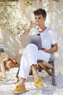 Young man with laptop drinking water while sitting on chair against wall - UKOF00091