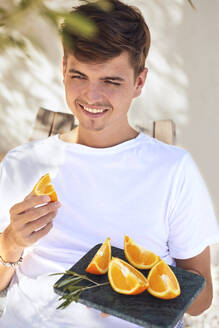 Smiling young man holding marble tray with slice of oranges against wall - UKOF00103