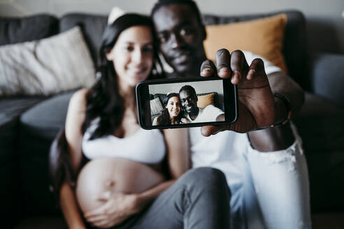 Smiling young man with pregnant woman taking selfie at home - EBBF01633