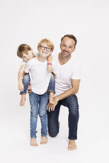 Boy piggybacking brother while standing by father against white background - SDAHF00993