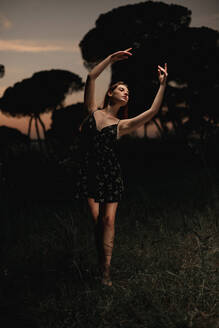 Elegant female ballet dancer in dress standing in meadow with raised arms and performing in dark park in Iceland - ADSF17775