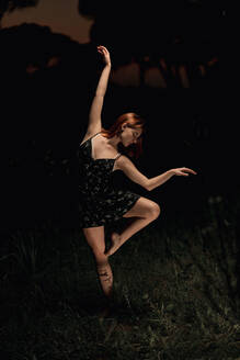 Elegant female ballet dancer in dress standing in meadow with raised arms and performing in dark park in Iceland - ADSF17778
