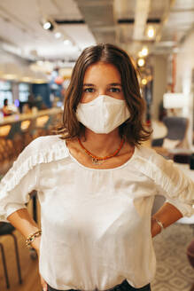 Serious young female employee in casual outfit and protective mask looking at camera while standing against blurred interior of modern coworking space - ADSF17837