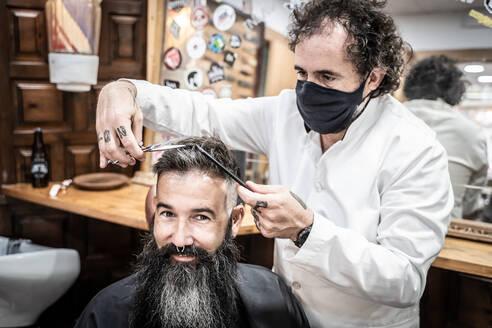 Brutal bearded mature male consumer smiling and looking at camera while professional barber in protective mask cutting hair with scissors and comb in barbershop - ADSF17855