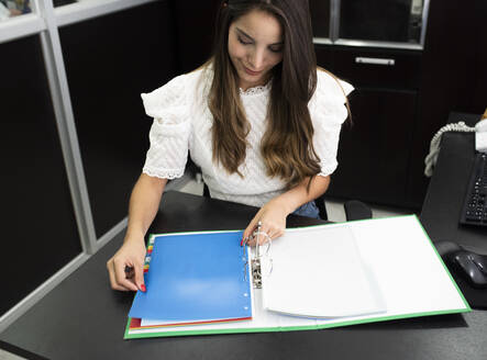 Businesswoman arranging papers in file while sitting at office - DSIF00214