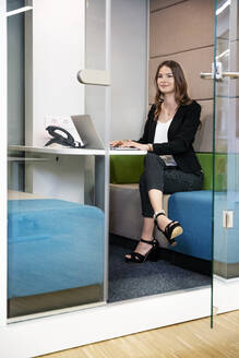 Smiling businesswoman using laptop while sitting in cabin at office - PESF02292