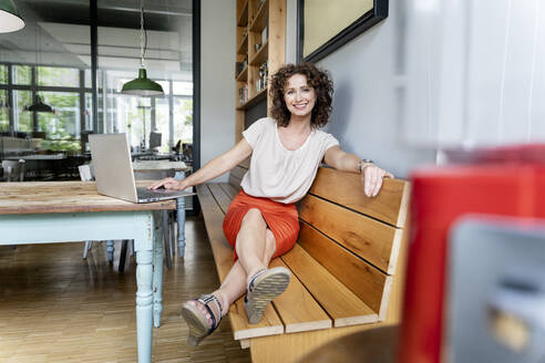 Businesswoman using laptop while sitting on bench at office - PESF02358