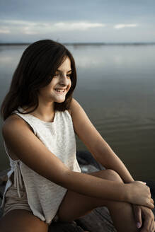Smiling girl sitting on jetty against lake - RCPF00364